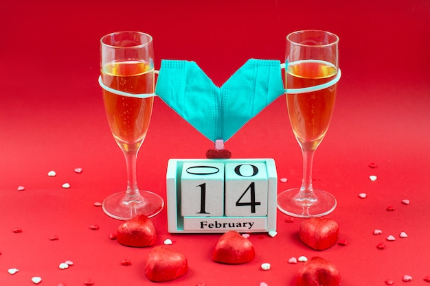 Two champagne glases, wooden calendar, candy and medical mask valentine on red. Premium Photo
