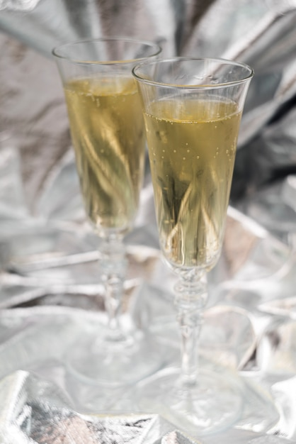 Two champagne glasses on blurred silver background Free Photo