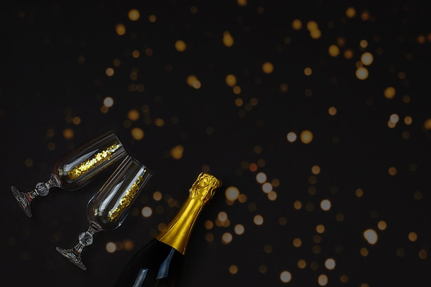 Two champagne glasses with confetti against bokeh on black background. Premium Photo