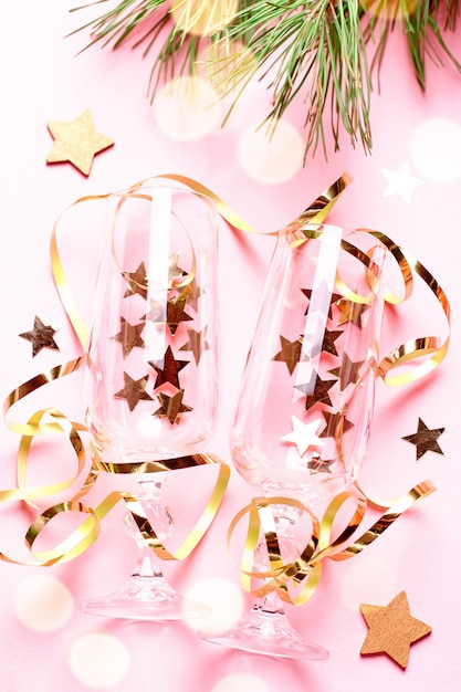 Two champagne glasses with confetti and streamers in pink and gold colors Premium Photo