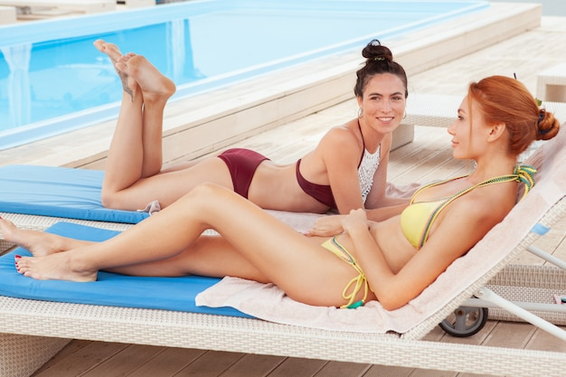 Two charming female friends relaxing by the swimming pool Premium Photo
