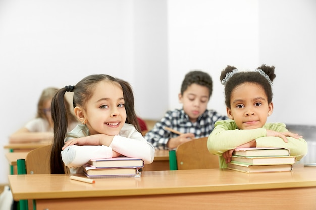 学校のテーブルに座っているとポーズの2人の魅力的な学生 Premium写真