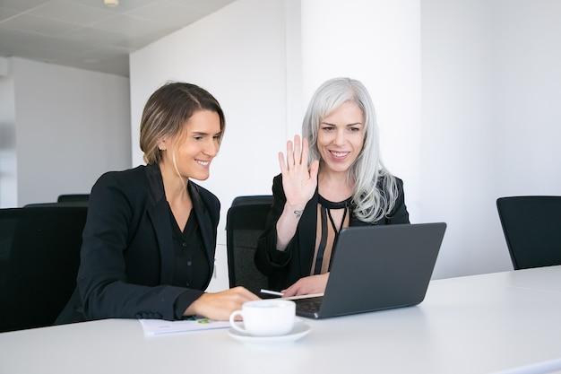 Две веселые коллеги-женщины, использующие ноутбук для видеозвонка, сидят за столом с чашкой кофе, смотрят на дисплей и машут руками. концепция онлайн-коммуникации Бесплатные Фотографии