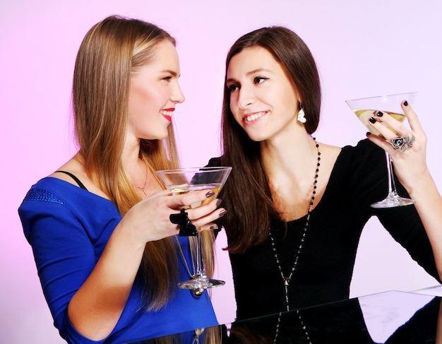 Two cheerful girlfriends with colorful cocktails Free Photo