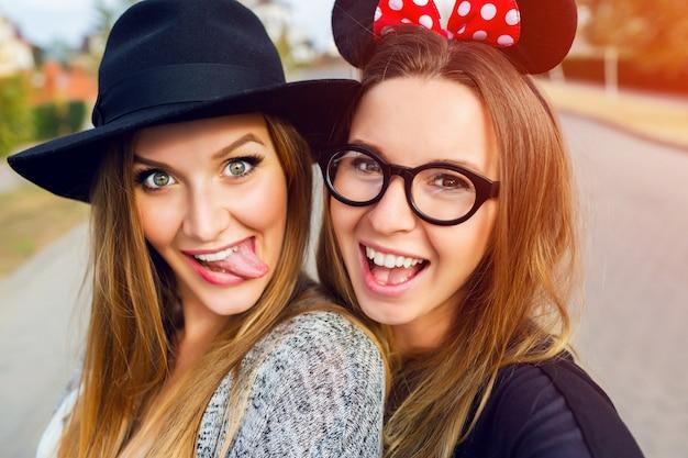 路上で楽しい2人の陽気な女の子。 無料写真