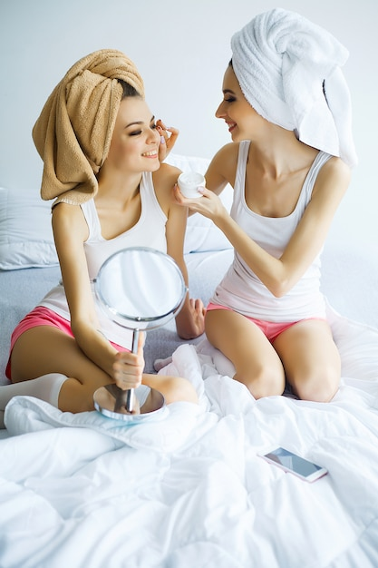 Two cheerful sisters with perfect skin siting on bed after bath Premium Photo