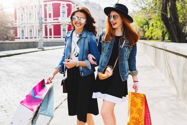 Две веселые женщины, делающие покупки в городе, гуляют по улицам Бесплатные Фотографии