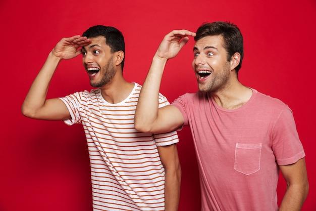 Двое веселых молодых людей стоят изолированно над красной стеной и смотрят вдаль Premium Фотографии