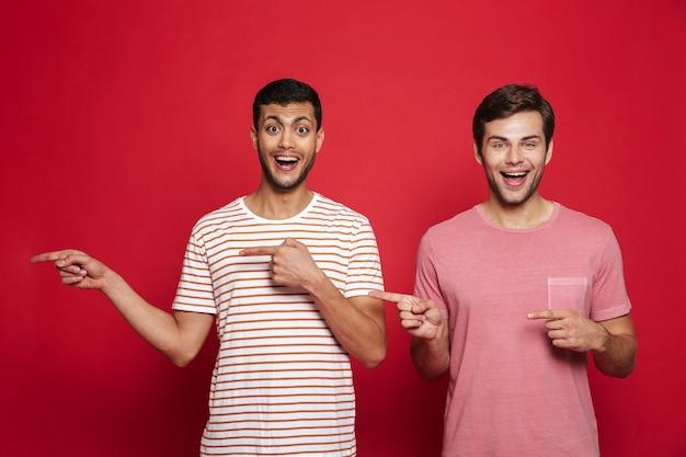 Два веселых молодых человека стоя изолированно над красной стеной, указывая на место для копирования Premium Фотографии