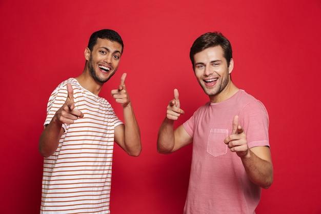 Два веселых молодых человека, стоящих изолированно над красной стеной Premium Фотографии