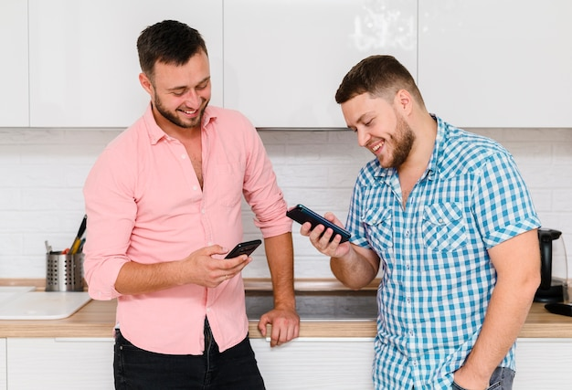 Two cheerful young people looking at their smartphones Free Photo