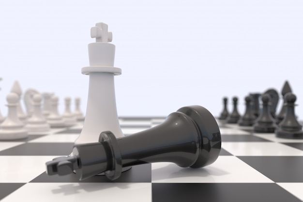 Two chess pieces on a chessboard. black king laying down and white king standing up. Premium Photo
