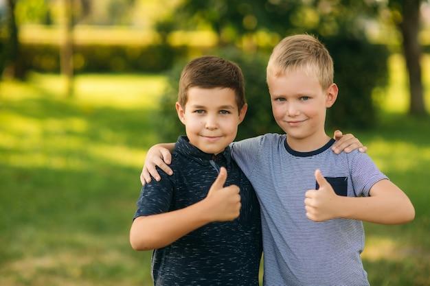 W parku bawi się dwoje dzieci.  dwaj śliczni chłopcy w koszulkach i szortach bawią się z uśmiechem.  jedzą lody, skaczą, biegają.  lato jest słoneczne.  Zdjęcie premium