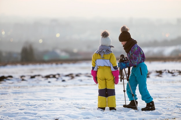 Two children boy and girl having fun outside in winter playing with photo camera on a tripod on snow covered field. Premium Photo