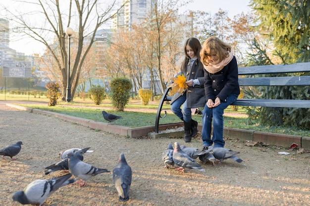 Двое детей девочки кормят птиц голубей в солнечный осенний день Premium Фотографии