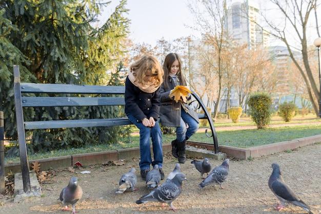 Двое детей женщины кормят птиц голубей в солнечный осенний день Premium Фотографии