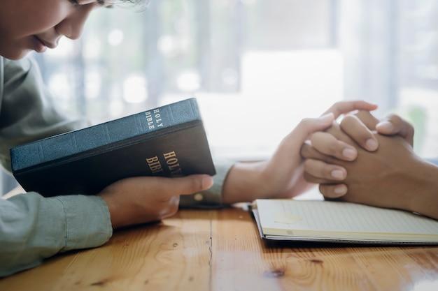 二人のクリスチャンが聖書を一緒に祈っています。 Premium写真