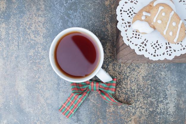 大理石の背景に2つのクリスマスクッキーとお茶。高品質の写真 無料写真