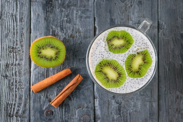 Two cinnamon sticks, chia seed pudding with kiwi fruit on a dark wooden table. the view from the top. flat lay. Premium Photo