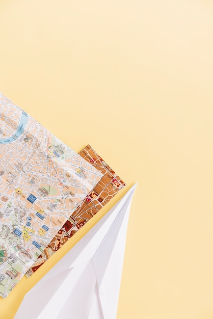 Two city maps with handmade paper airplane on the corner of the background Free Photo