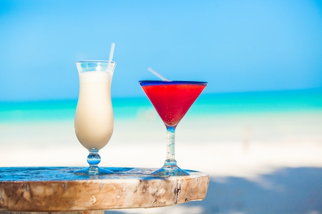 Two cocktails: pina colada and strawberry margarita on wooden table Premium Photo