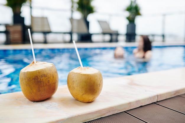 スパリゾートのプールの端にストローと2つのココナッツカクテル Premium写真