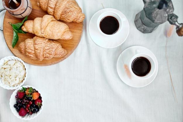 Две кофейные чашки и итальянская кофеварка с круассаном и фруктами над столом в домашней утренней концепции ритуалов завтрака, фоне еды образа жизни. Premium Фотографии