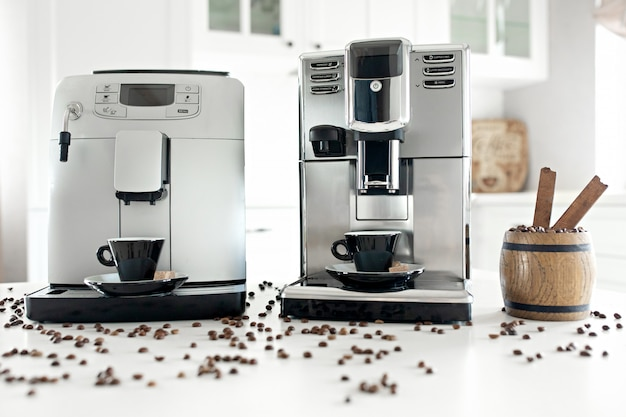 Two coffee machines in the home kitchen with a wooden container with coffee beans. Premium Photo