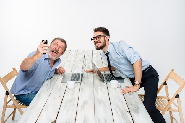 Two colleagues  taking the picture to them self sitting in office Free Photo