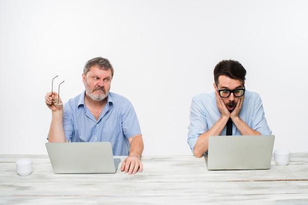 Два коллеги, работающие вместе в офисе на белом Бесплатные Фотографии