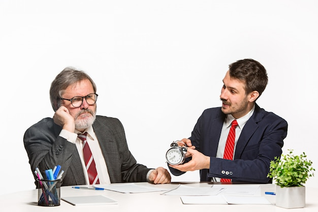 The two colleagues working together at office on white background. Free Photo