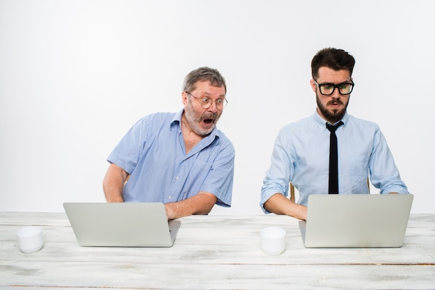 Two colleagues working together at office on white Free Photo