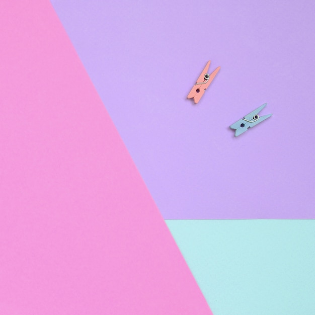 Two colored wooden pegs lie on texture background of fashion pastel violet, blue and pink colors paper in minimal concept Premium Photo