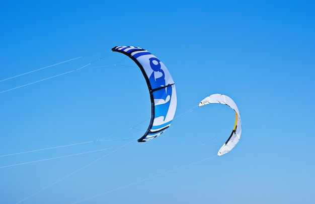 Two colorful kites of kiteboarding is flying in the blue sky Premium Photo