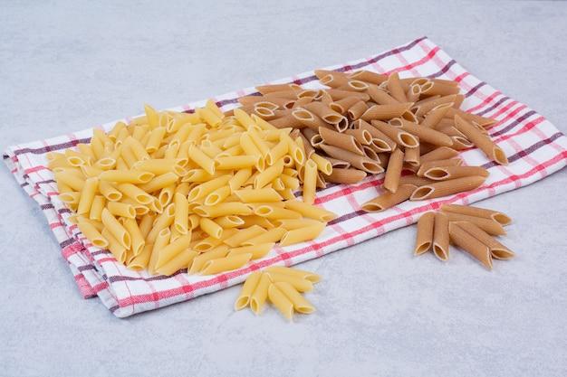 ストライプのテーブルクロスに生のペンネパスタ2色 無料写真