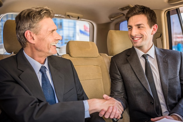 Two confident businessmen shaking hands and smiling. Premium Photo