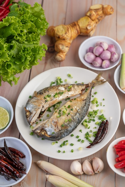 Two cooked mackerel, placed in a white dish, sprinkled with spring onions. Free Photo