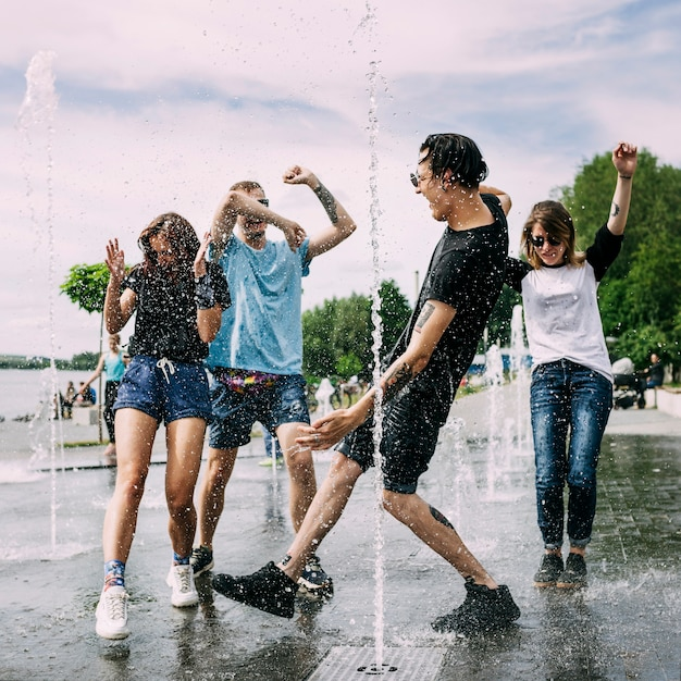 Two couples dancing in the fountain Free Photo