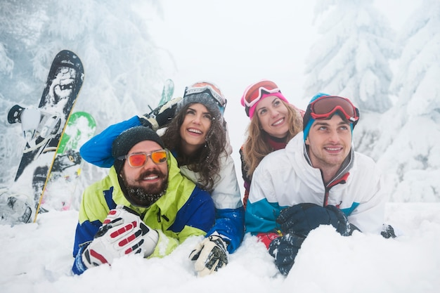 Two couples having fun and snowboarding Free Photo