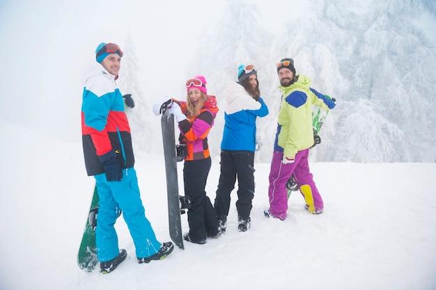 Due coppie che si divertono e fanno snowboard Foto Gratuite