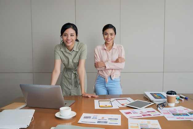 Two creative asian women posing in office, with laptop, documents and pictures on table Free Photo