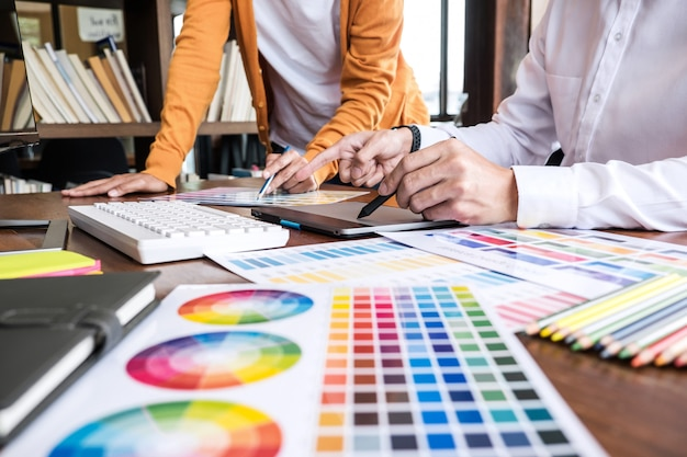 Two creative graphic designer working on color selection and color swatches Premium Photo