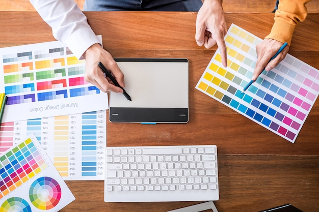 Two creative graphic designer working on color selection and swatches, drawing on graphics tablet Premium Photo
