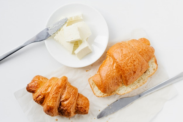 Two croissants and butter on white table, top view. Premium Photo
