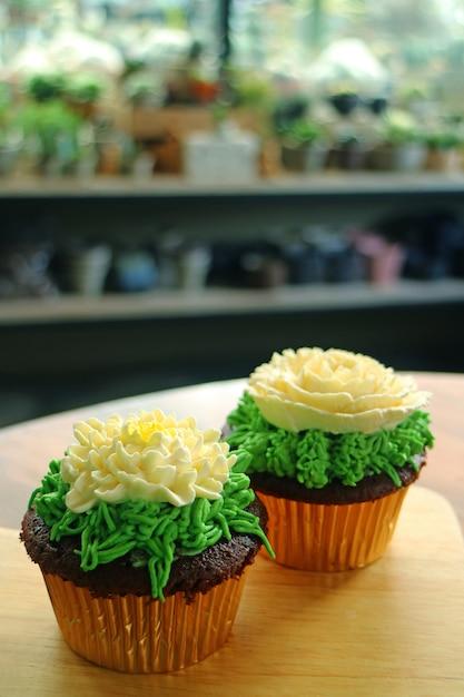 Two cupcakes topped with flower shaped whipped cream served on wooden table Premium Photo