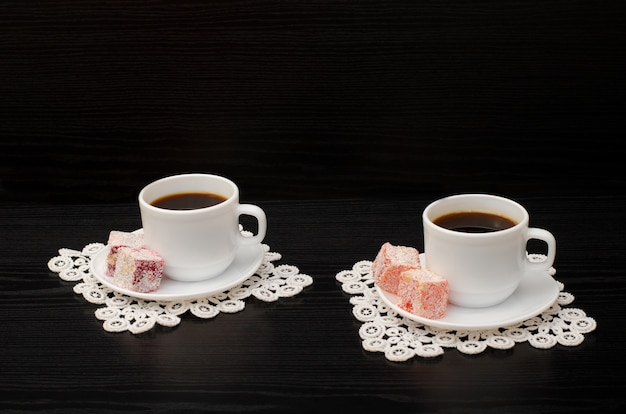Two cups of coffee on the lace napkins and  turkish dessert on a black Premium Photo