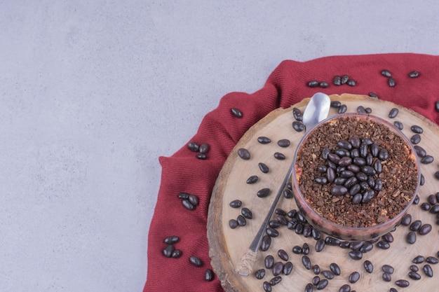 Due tazze di caffè con chicchi di cioccolato su un piatto di legno Foto Gratuite