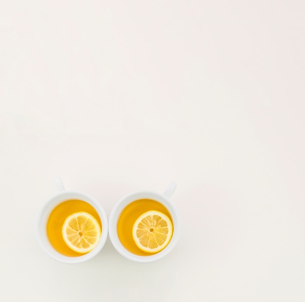 Two cups of green tea with lemon slice on white backdrop Free Photo