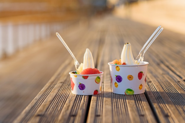 Two cups of ice cream with candies on sunset. Premium Photo