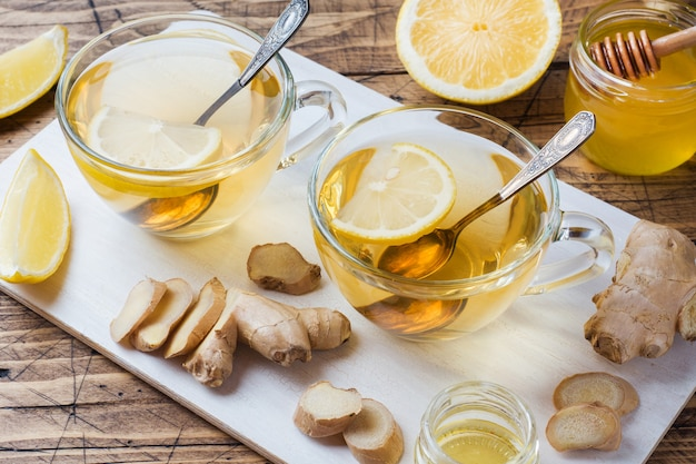 Two cups of natural herbal tea ginger lemon and honey Premium Photo